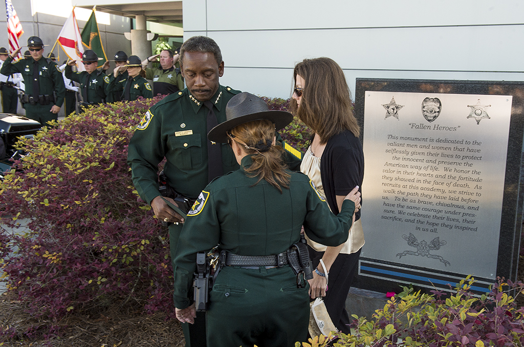 Orange County Sheriff Jerry Demings and Major Patty Wells assist Bridget Pine, widow of fallen Deputy Scott Pine, at the ceremony.