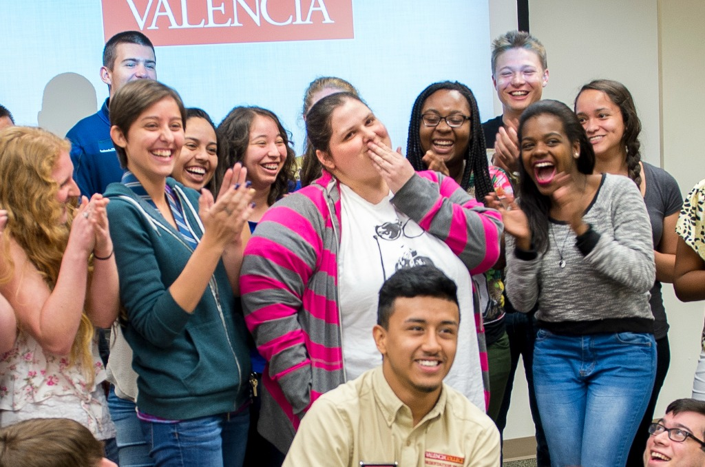 Faith Culhane (center) learns about her scholarship, with a little help from her fellow Valencia honors students.