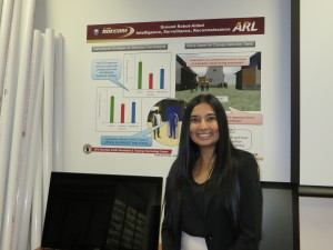Dr. Crystal Maraj displays a poster with findings of her research on the use of simulators in Army training.